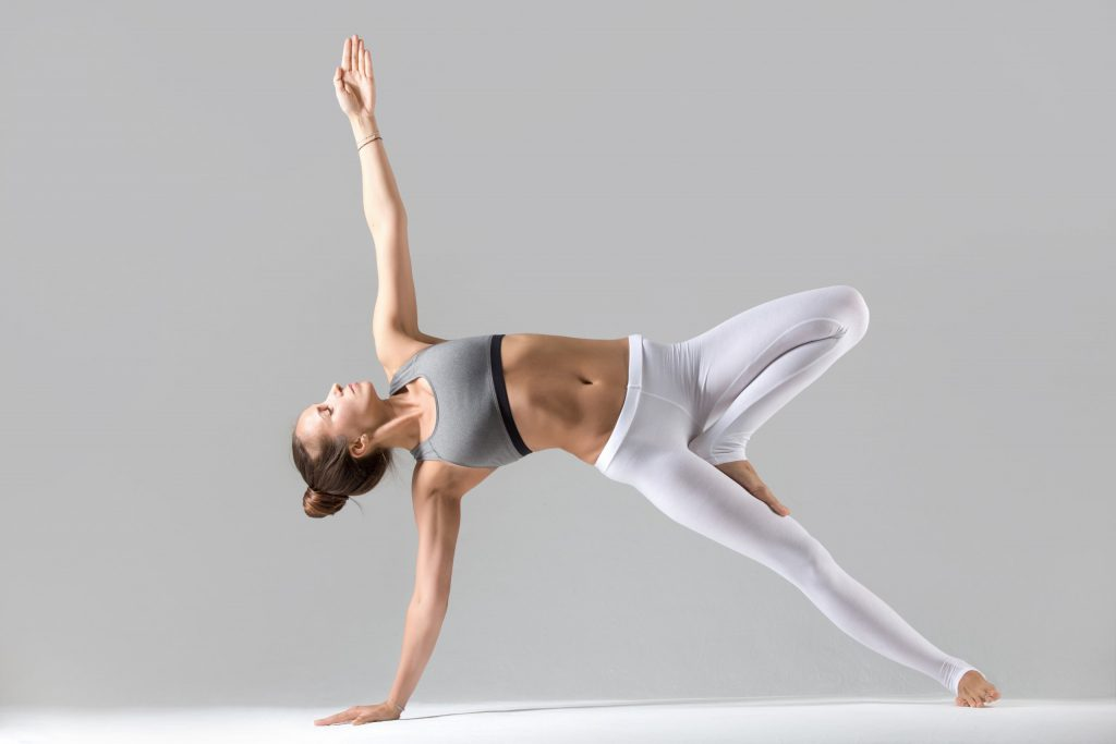young woman side plank pose grey studio background scaled 1